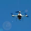 Fliegender Quadrokopter von schräg unten